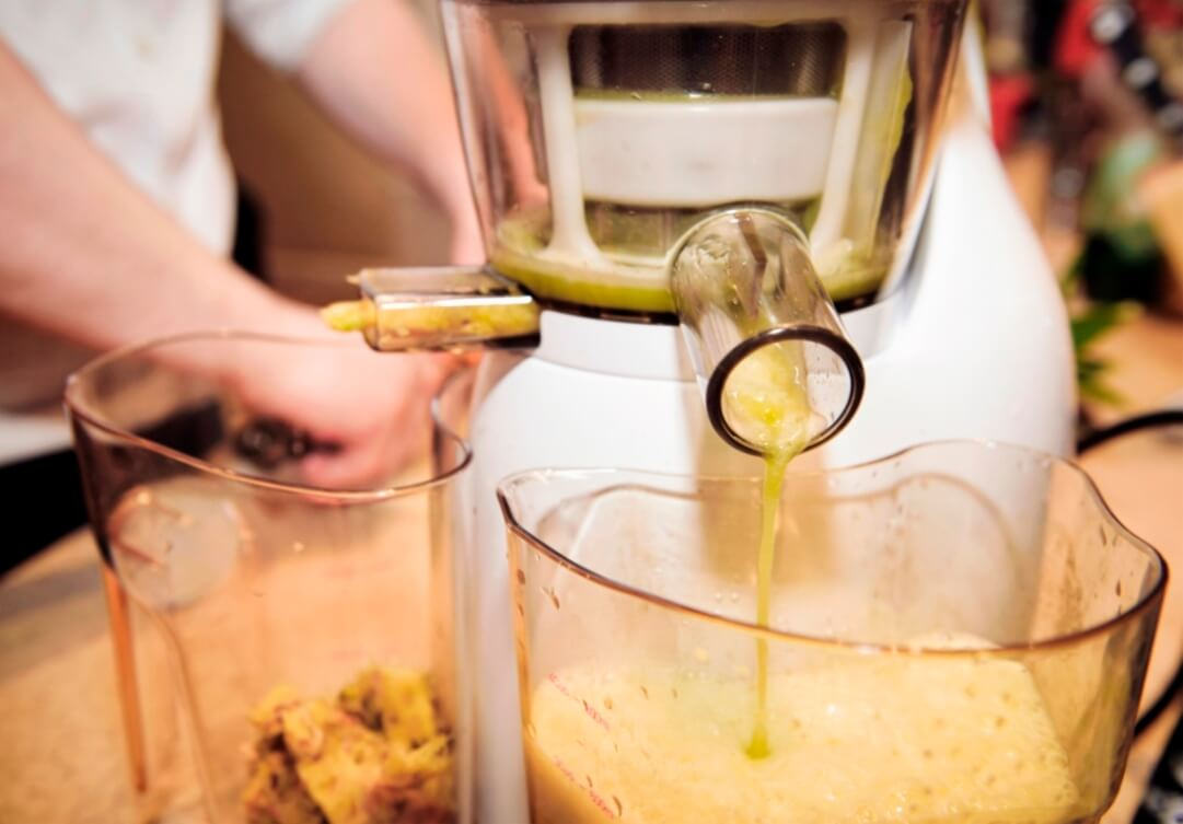 Close-up showing pineapple juice pouring out of a domestic juicing machine, with the pulp being collected to the left.
